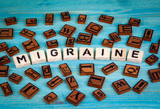 Migraine word written on wood block. Wooden alphabet on a blue background Stock Photo