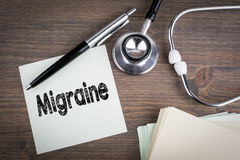Migraine, Workplace of a doctor. Stethoscope on wooden desk background Royalty Free Stock Images