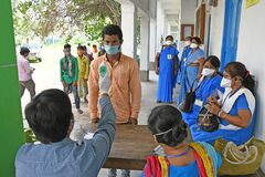 Migrant labourers rescued and confined at a `Burdwan Bidyarthi Bhaban High School` complex have queued up for health screening for