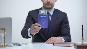 Migrant officer holding passport with dollars, payment for id card services. Stock footage stock video footage