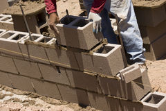 Migrant worker. Building cinder block wall in desert setting Royalty Free Stock Photography