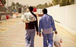 Migrant Workers in Doha, Qatar. Migrant workers in the Capital of Qatar, Doha, walking besides a construction place Royalty Free Stock Photos