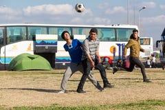 Migranten en vluchtelingenspelvoetbal in het parkeerterrein van een gas stock foto