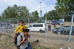 Migranten vom Mittlere Osten, der an der ungarischen Grenze wartet Lizenzfreie Stockfotografie