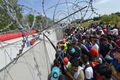 Migranten vom Mittlere Osten, der an der ungarischen Grenze wartet Lizenzfreie Stockbilder