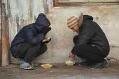 Migrants in Belgrade during winter. Belgrade, Serbia - January 10, 2017: A migrant eats free food during a snowfall outside a derelict customs warehouse. Migrant Stock Images