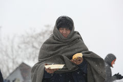 Migrants in Belgrade during winter. Belgrade, Serbia - January 10, 2017: A migrant eats free food during a snowfall outside a derelict customs warehouse. Migrant Royalty Free Stock Image