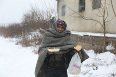Migrants in Belgrade during winter. Belgrade, Serbia - January 10, 2017: A migrant eats free food during a snowfall outside a derelict customs warehouse. Migrant Stock Photography