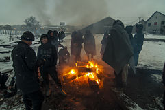Migrants are heated over a fire in the snow and cold weather royalty free stock photography