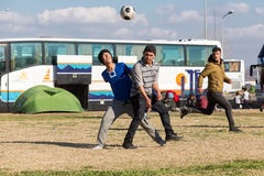 Migrants and refugees play football in the parking lot of a gas Stock Photo