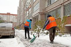 Migrants workers sweep snow in winter in Europe stock image