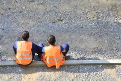 Migrants workers in yellow and orange vests resting by the road. They are sitting on the sidelines. Repair the road. Copy space. royalty free stock photography