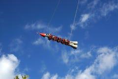 Migrar em um foguete em um parque de diversões headfirst contra o céu azul, resto extremo fotografia de stock royalty free