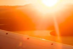 Migrar a opinião do curso de uma asa do avião com por do sol imagens de stock