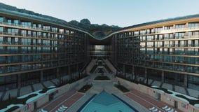 Migrar sobre a grande piscina azul do hotel de Mriya da elite, por do sol morno do verão filme