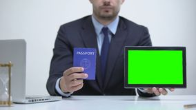 Migration agent holding passport and tablet, tourist visa application online. Stock footage stock video footage