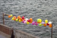 Soft baloons in a row and concrete barriers with gray sea background: Soft and hard borders concept. stock photos