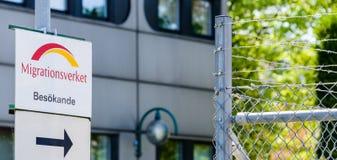 Migrationsverket,指向铁丝网篱芭的访客的一个箭头 非常最近有所有难民的一张符号图片 库存照片
