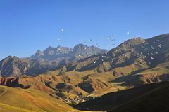 Migratory birds flying by red mountain. Mountains with red color under morning sunshine, located in Qilian mountains Royalty Free Stock Photos