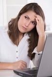 Migrena: bizneswomanu chrobotliwy czoło z laptopem Obrazy Stock