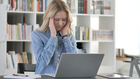 Migrena, młoda kobieta z głowa bólem Pracuje na laptopie zbiory