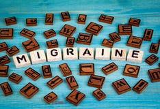 Migreny słowo pisać na drewnianym bloku Drewniany abecadło na błękitnym tle Zdjęcie Stock