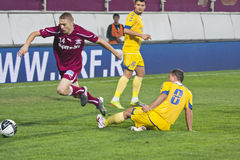 Mihai Roman Tackled by a Petrolul Opponent. Mihai Roman tackled by a Petrolul team's opponent  in Rapid Bucharest vs. Petrolul Ploiesti in Romanian Cup, 21 Royalty Free Stock Images