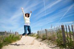Miidle ha invecchiato la donna che salta sulla spiaggia fotografie stock libere da diritti