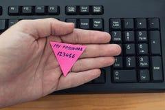 Mijn die wachtwoord 123456 op document nota door mensenhand wordt gehouden boven computertoetsenbord royalty-vrije stock afbeeldingen