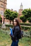 Mijn universitair leven Gelukkige leuke jonge studente met de boeken van de rugzakholding en het lopen bij collage stock foto