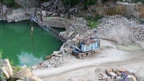 Mijnbouw in de granietsteengroeve Werkende mijnbouwmachine - oude kraan stock videobeelden