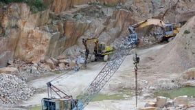 Mijnbouw in de granietsteengroeve Werkende mijnbouwmachine - oude kraan en graver stock footage