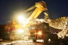 mijnbouw het graniet of het erts van de graafwerktuiglading in stortplaatsvrachtwagen stock foto's