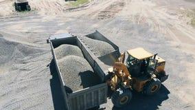 Mijnbouwplaats met de voertuigen die puin vervoeren stock video
