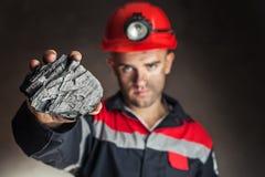 Mijnwerker die stuk van steenkool tonen royalty-vrije stock fotografie