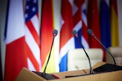 Mikes on tribune. Empty tribune with microphones in congress hall Royalty Free Stock Images