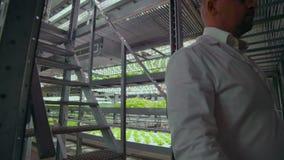Mikrobiologia w białych żakietach iść na nowożytnym gospodarstwie rolnym z laptopami i pastylkami studiuje rezultaty testy i kole zbiory wideo