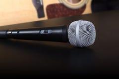 Mikrofon auf dem schwarzen Schreibtisch und mit Akustikgitarre auf verwischt Lizenzfreie Stockfotos