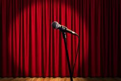 Mikrofon auf Stadium unter Scheinwerfern mit rotem Vorhang Lizenzfreie Stockfotos