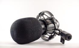Mikrofon framme av en vit bakgrund Royaltyfria Bilder
