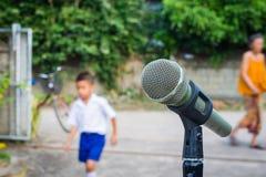 Mikrofon i bakgrunden av suddigt utomhus- med folk Arkivbild