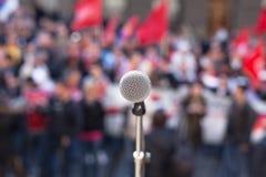 Mikrofon i fokus mot den oigenkännliga folkmassan av folk Arkivfoton