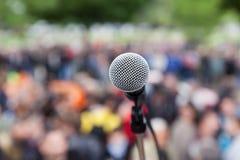 Mikrofon i fokus mot den suddiga folkmassan protest Arkivfoton