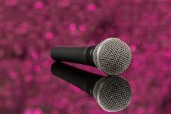 Mikrofon im defocus Rosahintergrund Stockbilder