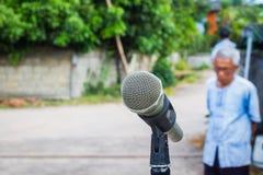 Mikrofon im Hintergrund von unscharfem im Freien mit altem Mann an Stockbild