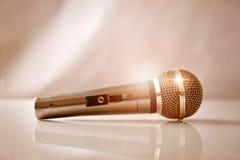 Mikrofon mit goldenen Reflexionen auf einem weißen Glastisch Lizenzfreie Stockfotos
