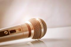 Mikrofon mit goldenen Reflexionen auf einem weißen Glastisch closeu Stockfotos