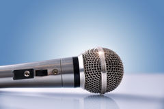 Mikrofon mit Reflexionen auf weißem Glastisch und Blau backgr Lizenzfreie Stockbilder