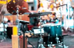 Mikrofon mit Trommeln und anderen Musikinstrumenten auf einem Stadium im Freien für die Ausführung von Musik Fokus auf dem Mikrof stockbilder