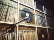 Mikrofon mit Vinylaufzeichnungs-Regal auf Hintergrund stockfoto